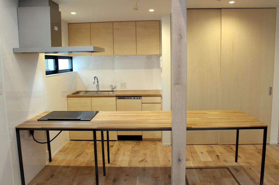 造作したオーダーキッチンと、IHクッキングヒーターを埋め込んだキッチン一体型のダイニングテーブル。