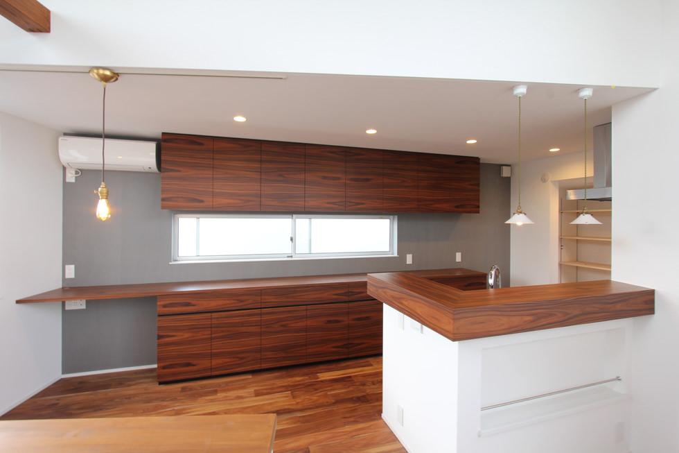 パープルウッドの突板を使った壁面収納とキッチンカウンター