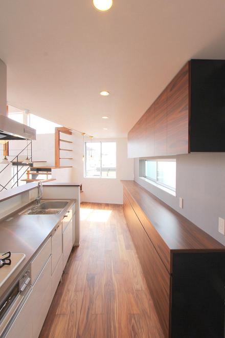 キッチンの奥から収納とシンクを写した写真