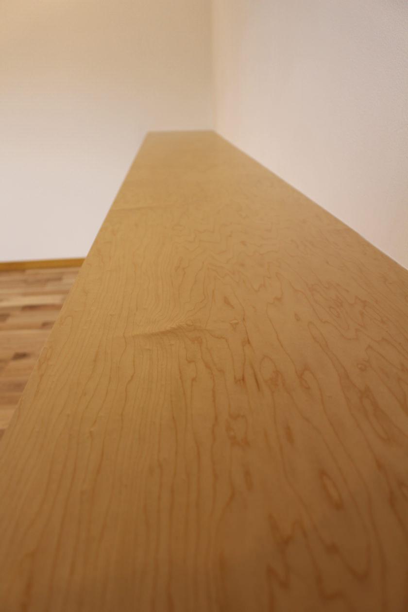 落ち着いた木目と明るい色味のメイプルのロータリー突板を使用した玄関収納の天板。