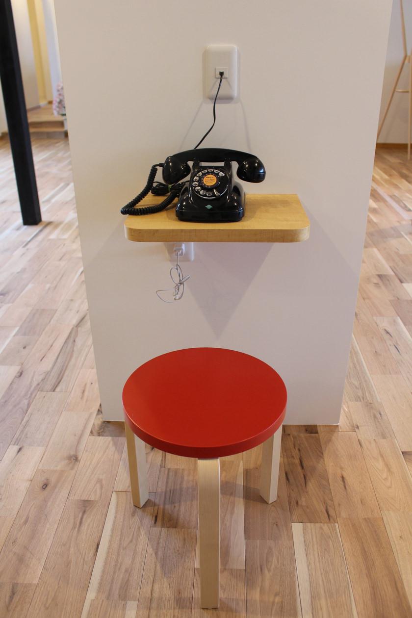アップル突板を使用して製作された電話台が書棚の側面に設置されている。電話台の上にはレトロな黒電話が乗せられ、その手前には赤い座面のスツールが置かれている。