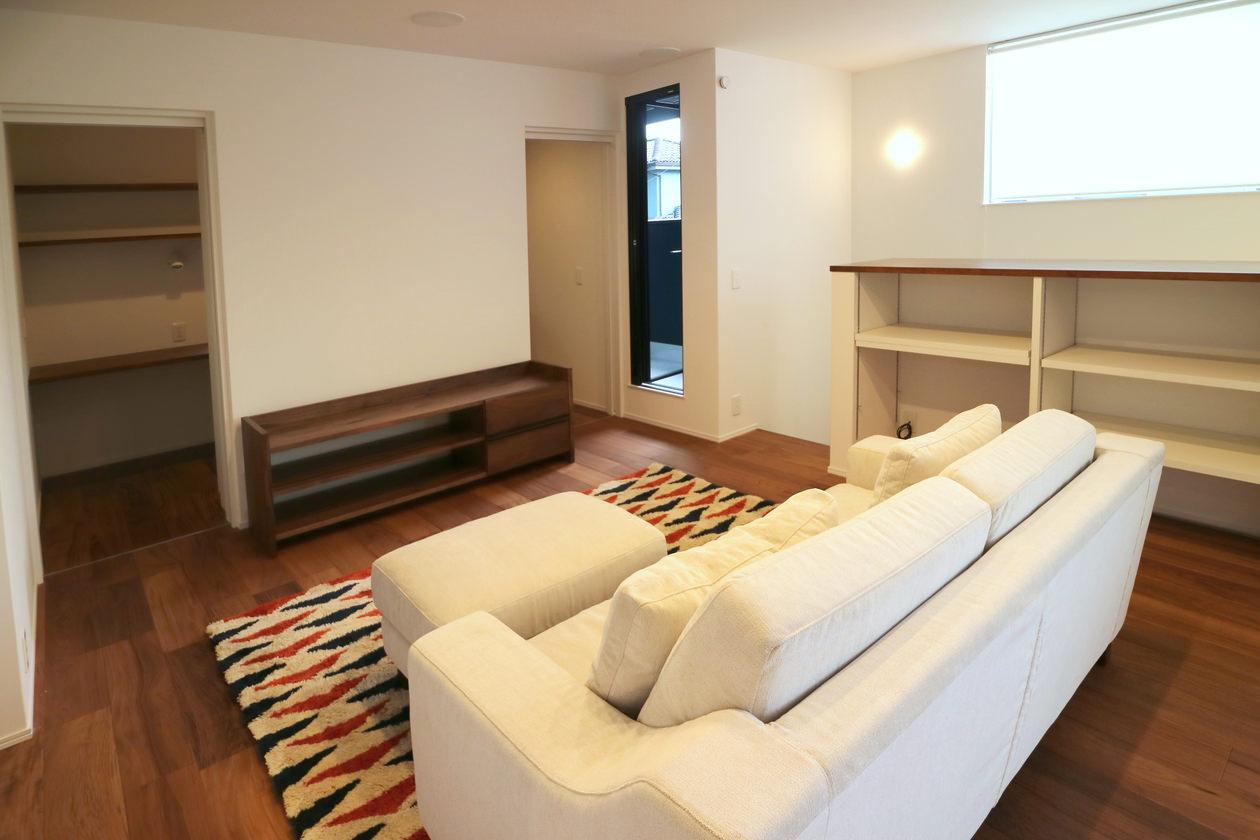 無垢材のTVボードは、ご主人の書斎スペースへつながる両サイドの扉に干渉せず、ホームシアターにも対応できるサイズのものを