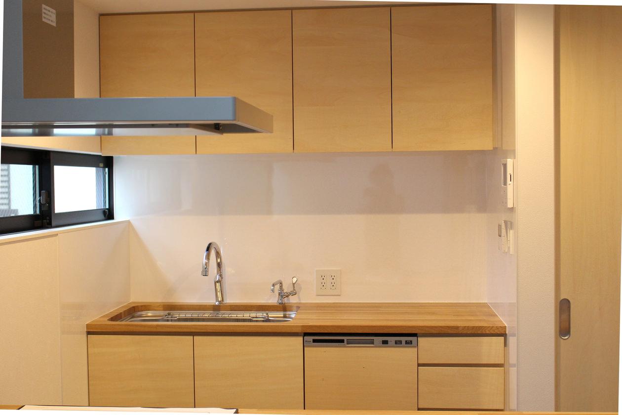 ウッドトップの造作キッチンとキッチン収納。キッチンの天板はオーク集成材で、吊戸棚とキッチンの扉材はシナ突板で製作している。