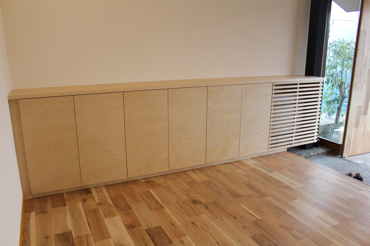 オーダー家具・メイプル材を使って製作し、オフィスのエントランスに造作した玄関収納。空調機はルーバーで目隠ししている。