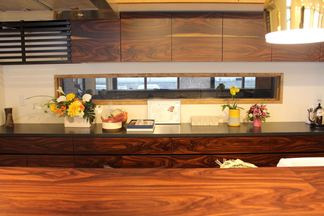 造作キッチン収納を正面から見た写真。左端のエアコンを目隠しする木製ルーバーはブラックで仕上げ、違和感なく馴染ませています