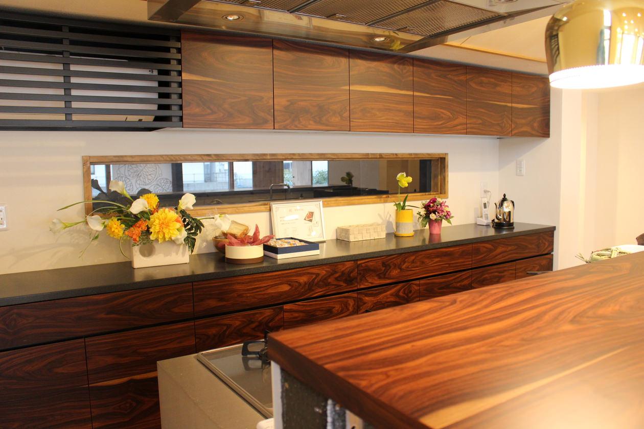 造作キッチン収納を斜めからみた写真。パープルウッドの木目、人工大理石、ゴールドの照明で高級感のある仕上りに