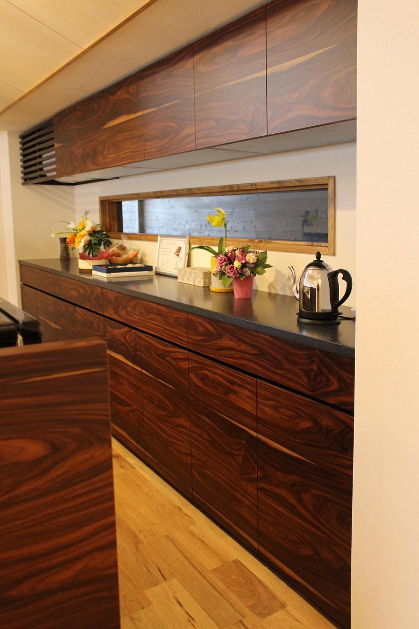造作キッチン収納。吊戸棚とカウンターボードの木目を揃えて突板を貼っている。カウンター収納の天板はブラックの人工大理石で製作