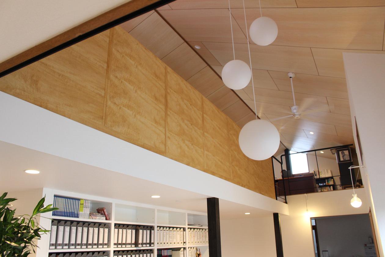 2階の飾り棚を1階から見上げている画像。白い壁と書棚とのコントラストが美しい。