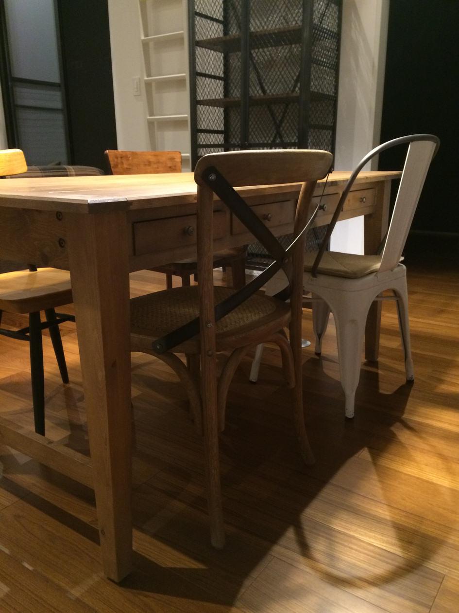 引き出しがアクセントになった木製テーブルとタイプの違う4脚の椅子を合わせている